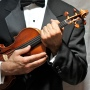 man in tuxedo cradling violin
